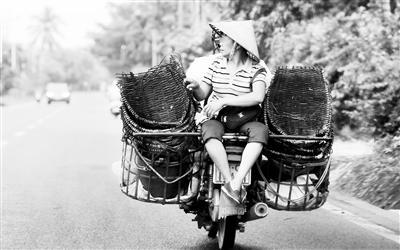 危险! 琼海一妇女搭便车 反向挤坐在摩托车后座上