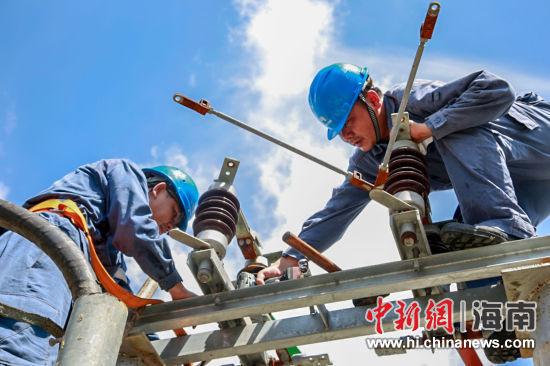 图为琼海供电局工作人员对设备进行维护。